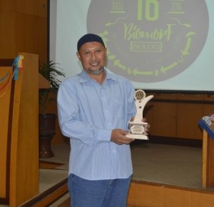 Drs. H. Hadi Sasongko memegang plakat sebagai dosen terfavorit